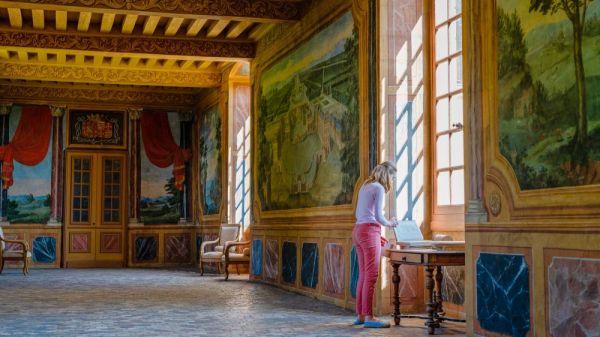 Une fille qui observe les arts de la galerie des chateaux du Roy